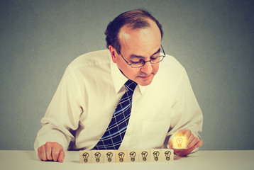 Middle aged business man sitting at table desk with yellow bright light bulb idea