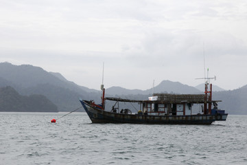 Thai fishing boats in the sea on a background of mountains