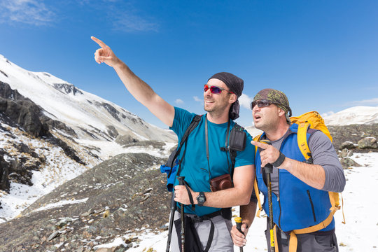 Tourists mountaineers snow mountains pointing finger looking sur