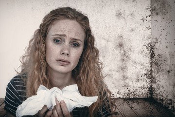 Composite image of portrait of sick woman holding paper tissue