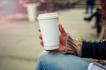 Coffee to go / Woman drinking coffe on the street. Close up