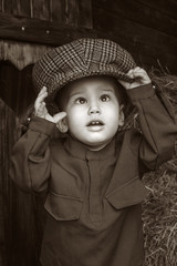 Retro! One year baby in Second World War russian uniform and driver cap. Wooden background, close up.