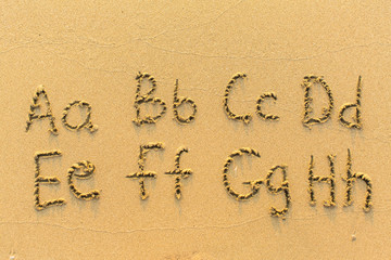 Alphabet written by hand on sandy beach (letters from A to H)