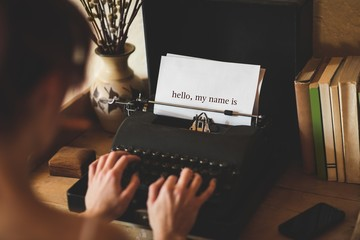 Hello, my name is against young woman using typewriter