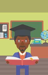 Man in graduation cap holding book.