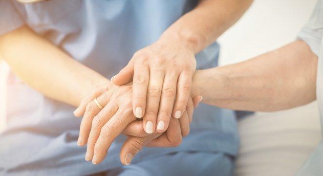 Composite image of nurse holding patient hand