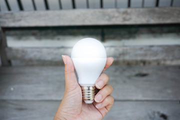 Bright LED bulb in hand with wooden bench background
