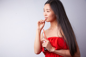 Chinese woman drinking carbonated drink through a straw