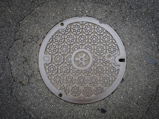 Circle steel manhole cover on asphalt street