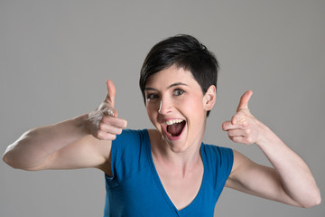 Studio portrait of excited energetic brunette beauty pointing finger towards camera over gray background