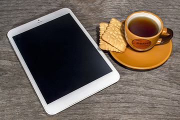 Cup of coffee with biscuits and tablet on wood