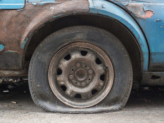 Close up flat tire of old car park on the street