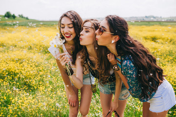 3 beautiful hippie girl in a field of yellow flowers