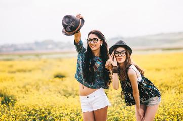 2 beautiful hippie girl in a field of yellow flowers
