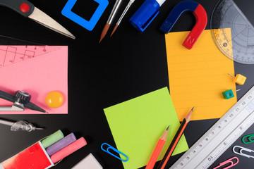 Back to School. Office objects over blackboard background.