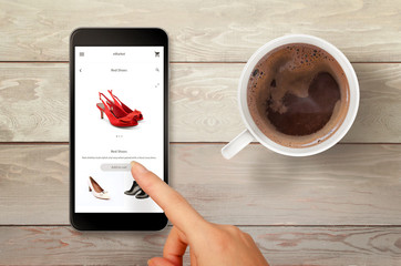 Woman shopping shoes with smart phone. Top view scene with coffee.