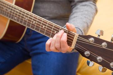 Hände eines jungen Mannes der Gitarre spielt