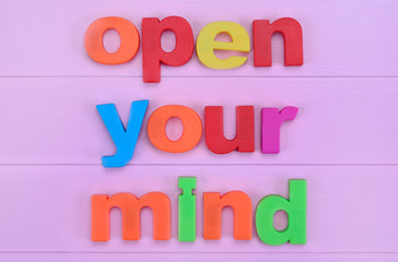 Words Open your mind on pink table