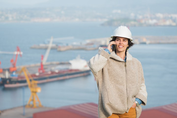 successful independent engineer smiling woman on industrial harbor with safety helmet talking on the phone. Pioneer woman at work.