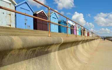 Sea defenses railings and beach huts Suffolk England.