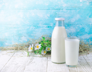 A bottle of rustic milk and glass of milk on a wooden table on blue background