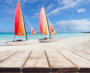 Wooden deck perspective with two colorful catamarans on white sa
