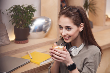 Cheerful young woman is drinking hot coffee