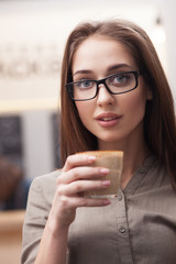 Cheerful young girl is relaxing with latte