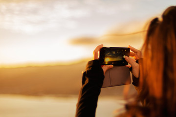 Brunette woman taking photo of sunset with smart phone, with focus on the screen