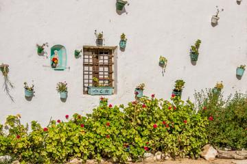 Blumendekoration mit Marienfigur an der Hausmauer