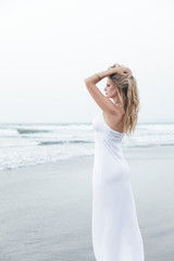 Young woman in long white dress looking at sea. Twilight time