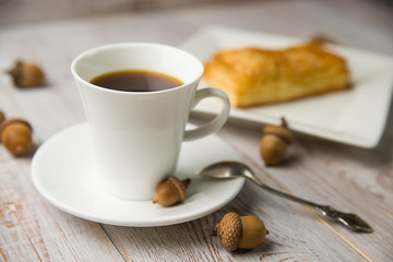 Cup of coffee, sweet buns and acorns