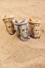 Dollar banknotes in hot desert sand