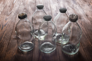 top view of dirty empty vintage transparent glass bottles with s