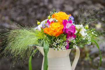 Beautiful yellow rose, pink alstroemeria, wax flower, white spray rose, green foliage flower arrangement in a jug. Wedding decor. Outdoor table decor. Vintage. Background.