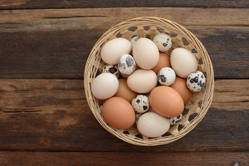 Overhead view of mix eggs in the basket on wooden table