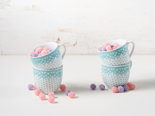 Fruit bonbons in coffee cups on white rustic background, copy space