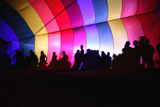 The silhouettes of visitors are etched onto the colorful interior of an inflating hot air balloon during the morning launch