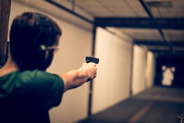 Man aiming pistol at target in indoor firing range or shooting range Wall mural