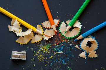 sharpener and wooden pencils with shavings on black