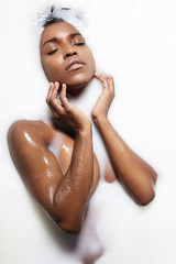 black woman touching her face in a milk bath