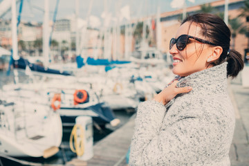 Woman enjoy with windy sunny spring day in the sea harbor, Genoa, Italy