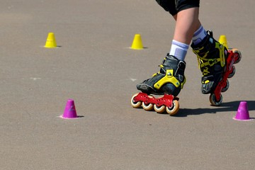 Leggs of roller skating young girl training with inline rollerblades.