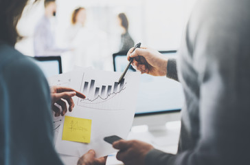 Business meeting image.Photo statistics document holding woman hand.Managers crew working with new startup project.Idea presentation,analyze marketing plans. Blurred background,film effect. Horizontal