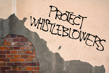 Handwritten graffiti Protect Whistleblowers on the wall, anarchist aesthetics. Appeal to expose illegal, unethical and not correct activities because of public good