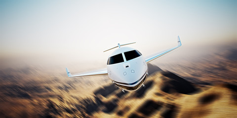 Photo of white modern and luxury generic design private jet flying in blue sky at sunrise.Uninhabited desert mountains background.Business travel picture.Horizontal,motion blurred effect.3d rendering