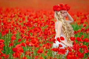 Beautiful girl in a red flowers field