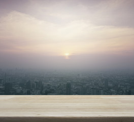 Fototapete - Empty wooden table with aerial view of cityscape at sunset, for