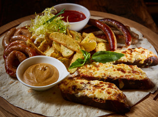 Assorted fried sausages, grilled potatoes, sauce Adjika, Mustard Sauce