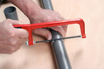 Plumber cutting pvc pipe with a saw